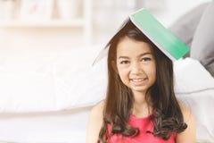 Ragazza asiatica felice con il Libro verde sopra la sua testa, Fotografia Stock
