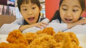 Ragazza asiatica felice con pollo fritto in ristorante video d archivio