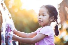 Ragazza asiatica felice del bambino divertendosi per aiutare l'automobile di lavaggio del genitore fotografia stock