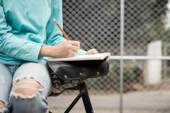 Ragazza asiatica femminile che scrive un taccuino mentre sedendosi una bicicletta fuori Immagine Stock
