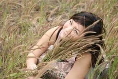Ragazza asiatica fra erba Fotografia Stock