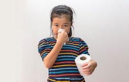 Ragazza asiatica malata con lo starnuto sul naso e la tosse fredda sulla carta velina immagine stock