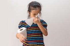 Ragazza asiatica malata con lo starnuto sul naso e la tosse fredda sulla carta velina immagine stock libera da diritti