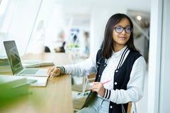 Ragazza asiatica nel coworking collegato ad Internet senza fili libero nell'aula della scuola Fotografie Stock