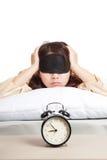 Ragazza asiatica sonnolenta con la maschera di occhio e la sveglia Immagini Stock