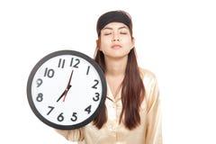 Ragazza asiatica sonnolenta con la tenuta della maschera di occhio un orologio Fotografia Stock