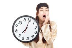 Ragazza asiatica sonnolenta con la tenuta della maschera di occhio un orologio Immagini Stock