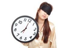Ragazza asiatica sonnolenta con la tenuta della maschera di occhio un orologio Immagine Stock