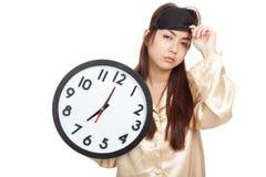 Ragazza asiatica sonnolenta con la tenuta della maschera di occhio un orologio Fotografie Stock Libere da Diritti