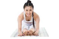 Ragazza asiatica sorridente in abiti sportivi che praticano in avanti piegare posa sulla stuoia di yoga Immagine Stock