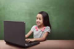Ragazza asiatica sorridente che utilizza computer portatile nell'aula Fotografia Stock