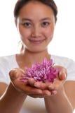 Ragazza asiatica sorridente con un fiore Fotografia Stock