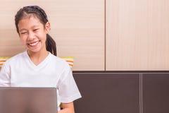 Ragazza asiatica sorridente felice che per mezzo del computer portatile per studiare su lei Fotografie Stock