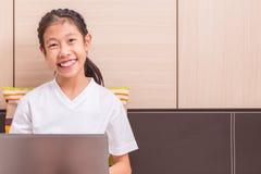 Ragazza asiatica sorridente felice che per mezzo del computer portatile per studiare su lei Fotografie Stock Libere da Diritti