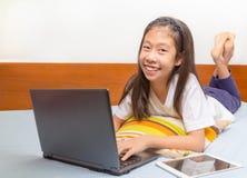 Ragazza asiatica sorridente felice che per mezzo della compressa del computer Fotografia Stock Libera da Diritti