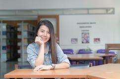 Ragazza asiatica sorridente sicura dello studente nell'università delle biblioteche Immagini Stock