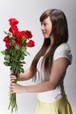 Ragazza asiatica sveglia che accetta i fiori Immagini Stock