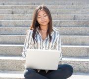 Ragazza asiatica sveglia che per mezzo di un computer portatile all'aperto Fotografia Stock Libera da Diritti
