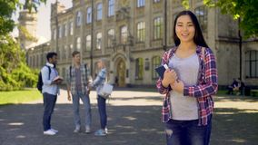 Ragazza asiatica sveglia che posa vicino alla costruzione dell'università, programma educativo internazionale video d archivio