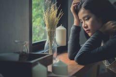 Ragazza asiatica sveglia che si siede dalla finestra con una sensibilità triste e sola fotografia stock