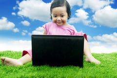 Ragazza asiatica sveglia che si siede sull'erba con il computer portatile Immagini Stock Libere da Diritti