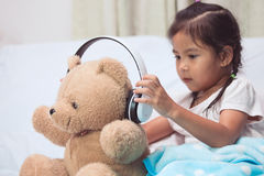Ragazza asiatica sveglia del bambino che gioca con il suo orsacchiotto con la cuffia Fotografia Stock