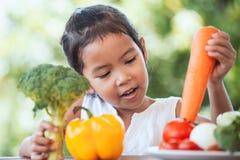 Ragazza asiatica sveglia del bambino che impara circa le verdure fotografia stock