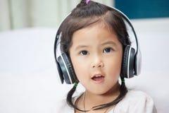 Ragazza asiatica sveglia del bambino in cuffie che ascolta la musica Immagine Stock