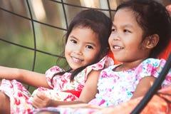 Ragazza asiatica sveglia del piccolo bambino due che gioca insieme le oscillazioni Fotografia Stock