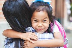 Ragazza asiatica sveglia dell'allievo con lo zaino che abbraccia sua madre con felicità dopo indietro dalla scuola immagini stock libere da diritti