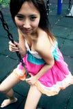 Ragazza asiatica sveglia su un'oscillazione Fotografia Stock