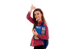 Ragazza astuta alla moda felice dello studente con lo zaino sulle sue spalle e cartelle per i taccuini in mani che mostrano i pol Fotografia Stock