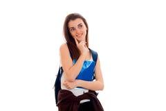 Ragazza astuta allegra dello studente in vestiti marroni di sport con lo zaino sulle sue spalle che sorride e che distoglie lo sg Fotografia Stock Libera da Diritti