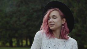 Ragazza astuta con i supporti alla moda di sguardo nelle pose alla macchina fotografica al parco archivi video
