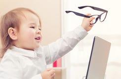 Ragazza astuta del bambino che indossa i grandi vetri facendo uso del suo computer portatile Immagini Stock