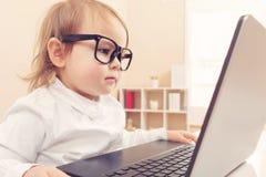 Ragazza astuta del bambino che indossa i grandi vetri facendo uso del suo computer portatile Immagine Stock