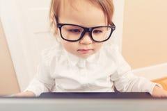 Ragazza astuta del bambino che indossa i grandi vetri facendo uso del suo computer portatile Fotografie Stock Libere da Diritti