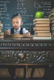 Ragazza astuta della scuola che legge un libro alla biblioteca Fotografia Stock