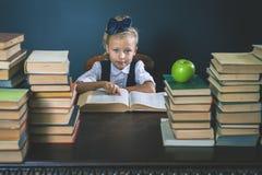 Ragazza astuta della scuola che legge un libro alla biblioteca Fotografie Stock Libere da Diritti