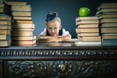 Ragazza astuta della scuola che si siede alla tavola con molti libri Immagini Stock