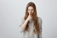 Ragazza astuta pronta per l'uso la sua conoscenza Ritratto di bella giovane donna abile che mette i vetri sul naso, guardante da fotografia stock
