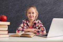 Ragazza astuta sveglia che si siede con il libro ed il computer portatile alla tavola Immagini Stock