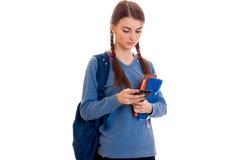 Ragazza astuta triste dello studente con lo zaino sulle sue spalle e cartella per i taccuini in sue mani che guardano giù isolate Fotografia Stock Libera da Diritti