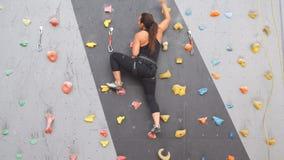 Ragazza atletica abbastanza giovane che scala su una parete dell'interno di scalata archivi video
