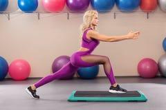 Ragazza atletica che fa allungando esercizio nella stanza di forma fisica Donna di sport nell'allenamento degli abiti sportivi Immagini Stock Libere da Diritti