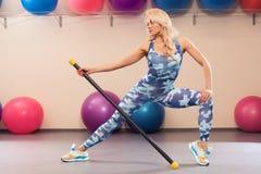 Ragazza atletica che fa allungando esercizio nella stanza di forma fisica Donna di sport nell'allenamento degli abiti sportivi Fotografia Stock