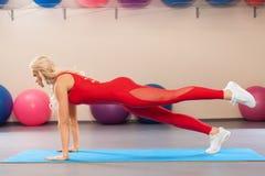 Ragazza atletica che fa esercizio del tavolato nella stanza di forma fisica Donna di sport nell'allenamento degli abiti sportivi Immagini Stock