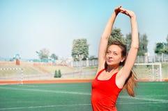 Ragazza atletica che sta con le sue mani dietro lei capa e che esamina macchina fotografica Fotografia Stock