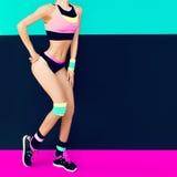 Ragazza atletica esile in abiti sportivi d'avanguardia luminosi Modo di forma fisica Fotografia Stock
