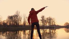 Ragazza atletica impegnata negli esercizi relativi alla ginnastica e nell'allungamento al tramonto sulla riva nel parco della mol stock footage